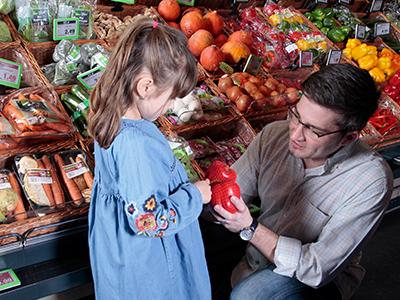 Vater und Tochter kaufen Paprika